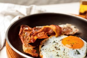 Frying pan with fried egg and bacon, closeup
